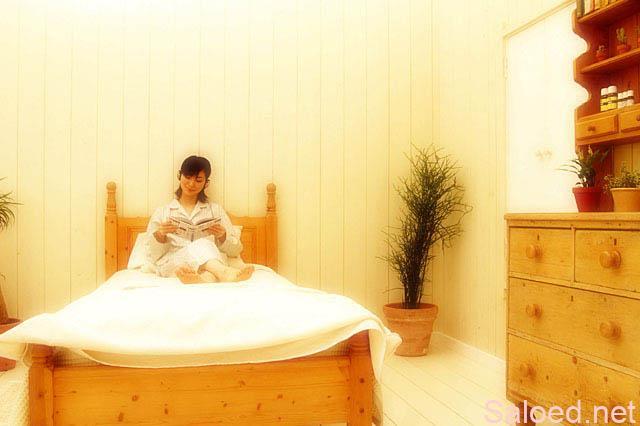 ベッドに座る女性 本を読む